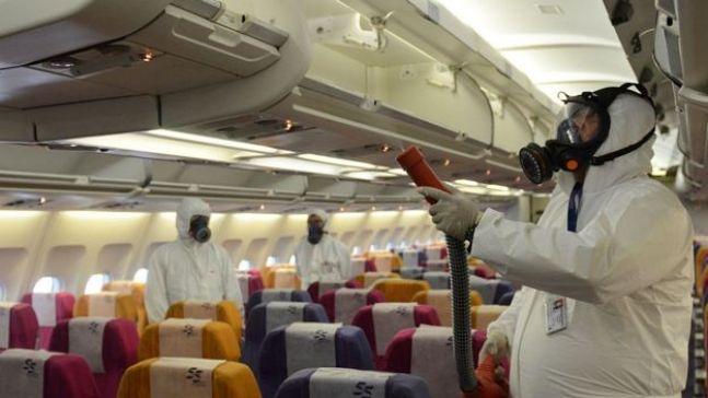 عامل يرش مواد تعقيمية داخل طائرة في تايلاند في عام 2015
