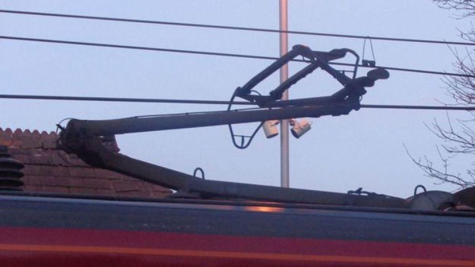 Mecanismo articulado encima de un tren que le transmite electricidad