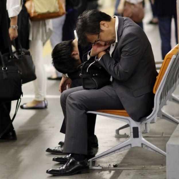 Ejecutivo dormido en un banco en una estación de metro