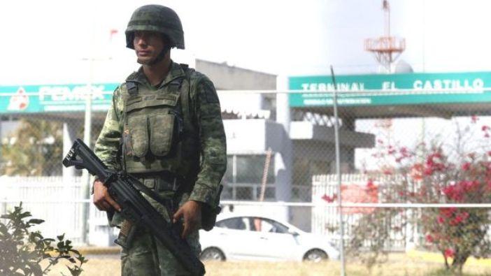 Militar de guardia frente a una gasolinera.
