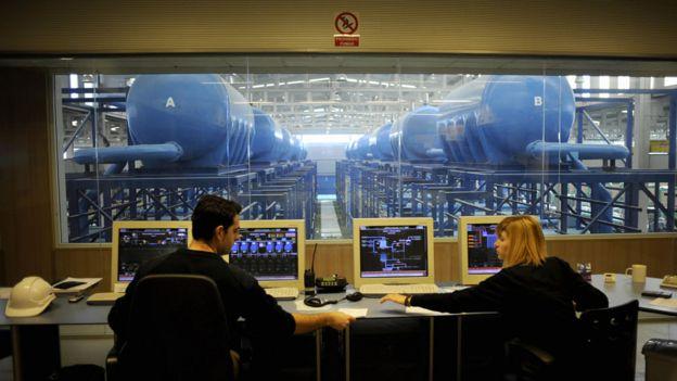 Dos personas en la sala de control de una planta de desalinización