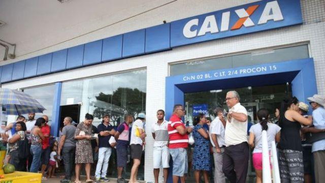Pessoas em pé, formando uma fila, em frente a uma agência da Caixa