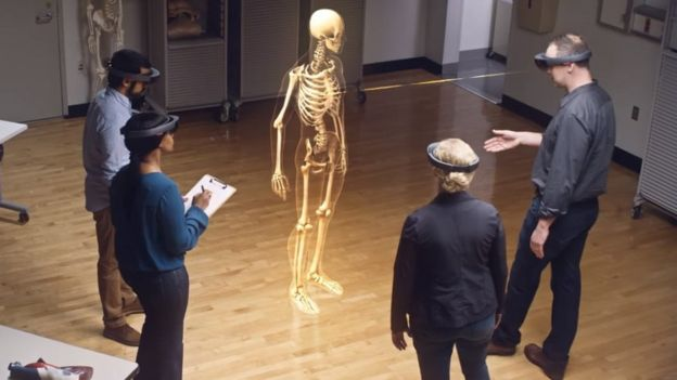 Students wearing headsets and looking at a virtual skeleton