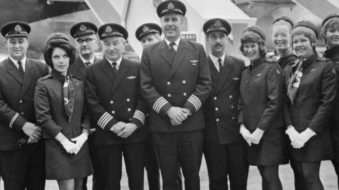 Captain Douglas Redrup of BOAC stands with members of his flight crew before taking off on the first scheduled flight.