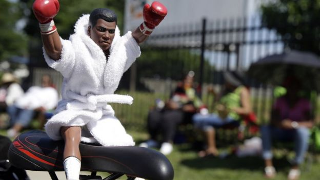 Muhammad Ali action figure sits on seat of bicycle - 10 June