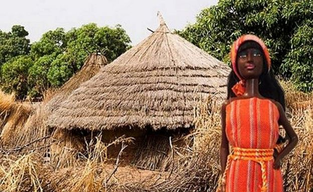 Barbie doll in front of a hut