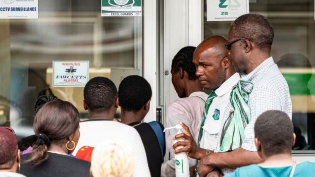 People getting their hands sanitised as they enter a bank