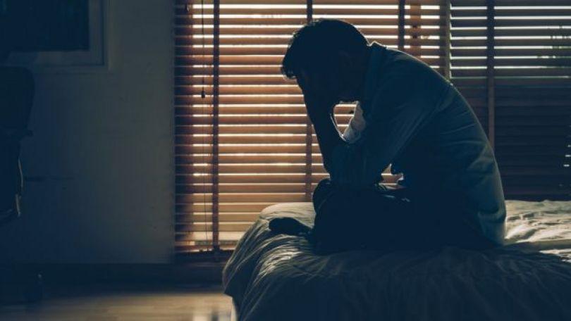Homem sentado na beira da cama