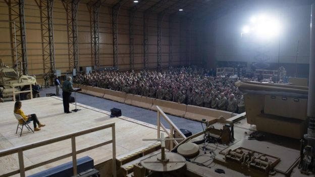 US President Donald Trump speaks to members of the US military as First Lady Melania Trump looks on during an unannounced trip to Al Asad Air Base in Iraq, December 26, 2018