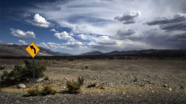 Paisagem desértica do Vale da Morte, sob um céu azul com nuvens brancas