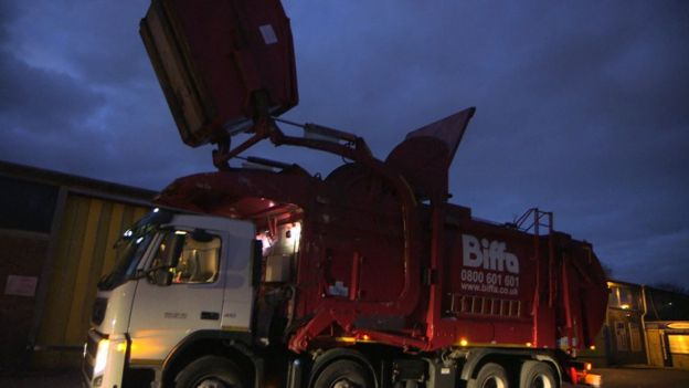 Biffa truck lift prepares to tip contents of recycling container into its compactor