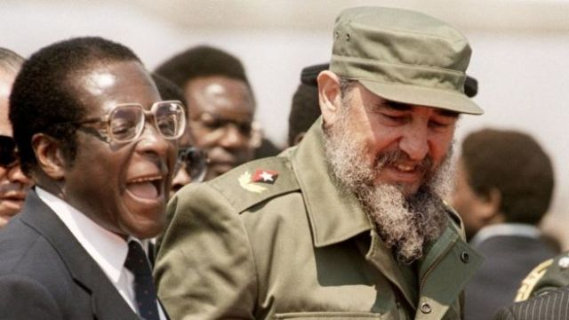 Robert Mugabe laughs as he stands next to Fidel Castro