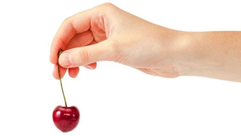 Mano sosteniendo una cereza.