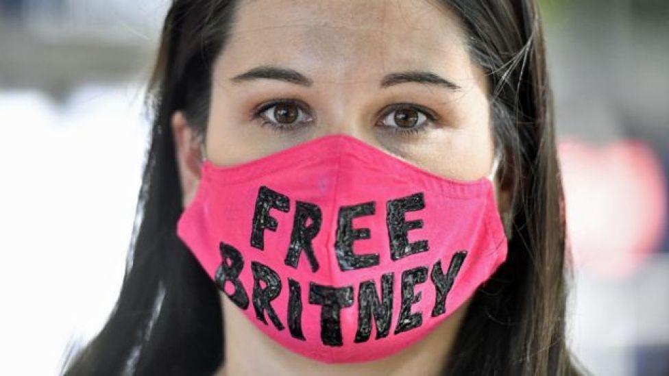 """Britney Spears fan wearing a """"Free Britney"""" mask outside court in July"""