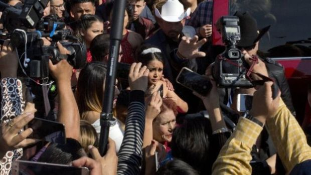Rubi Ibarra arrives at the site of a Mass that is part of her down-home 15th birthday party, surrounded by a horde of journalists, in the village of La Joya, San Luis Potosi State, Mexico, Monday, Dec. 26, 2016.