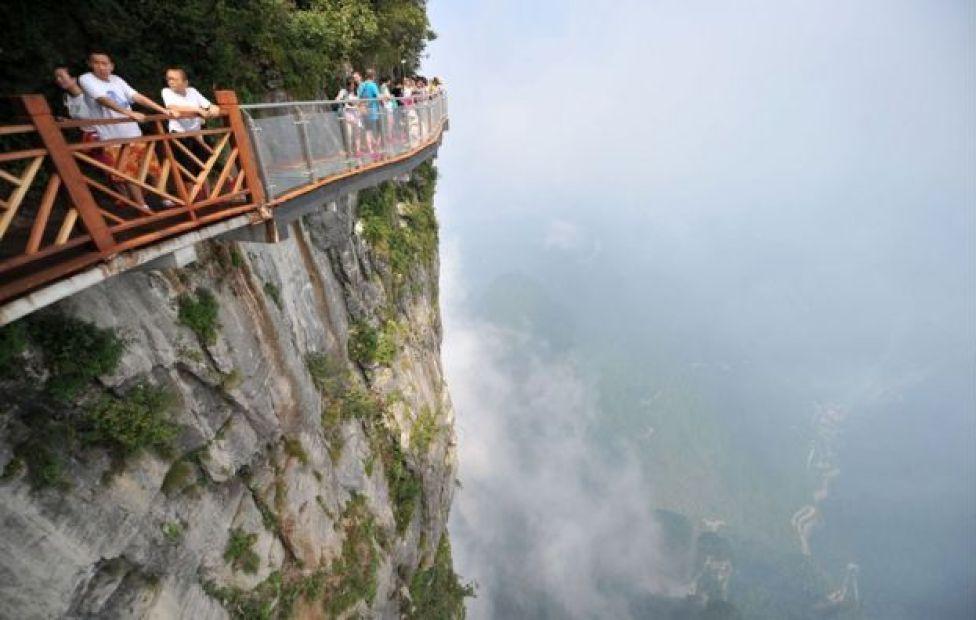 Gente camina sobre un puente de cristal en el Parque forestal nacional Zhangjiajie.