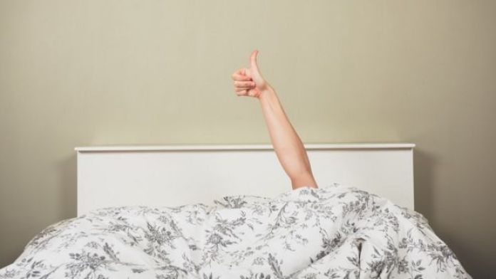 A young woman in a bed is giving thumbs up