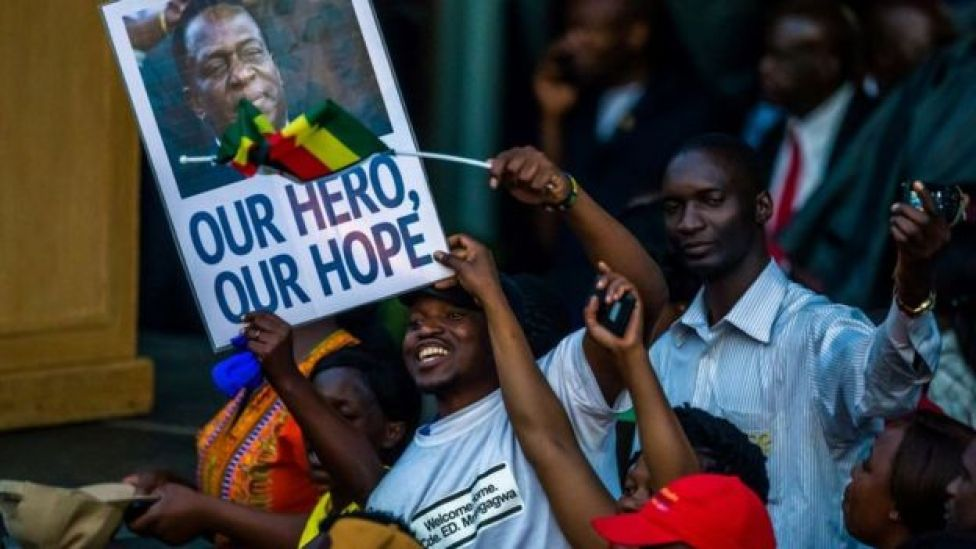 Supporters hold banner, wave Zimbabwean national flag and cheer as they gather to welcome Zimbabwe's incoming President Emmerson Mnangagwa upon his arrival at Zimbabwe's ruling Zanu-PF party headquarters in Harare on November 22, 2017