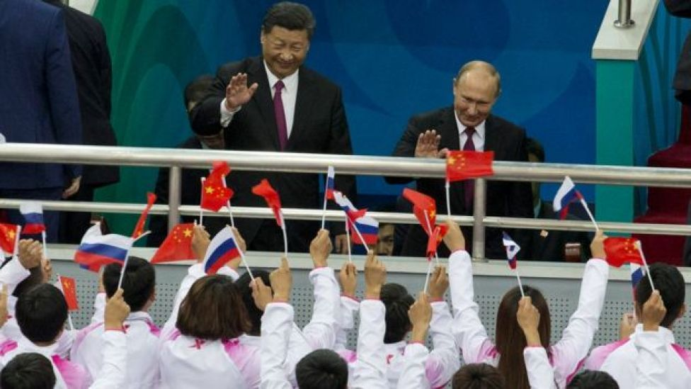 Russian President Vladimir Putin (R) and Chinese President Xi Jinping wave to spectators during a friendly match between Chinese and Russian youth Ice Hockey teams on June 8, 2018 in Tianjin, China