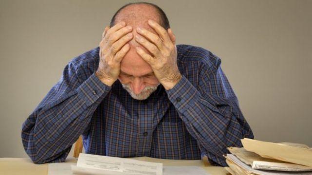 Homem idoso sentado à mesa, olhando papeis e com as mãos na cabeça