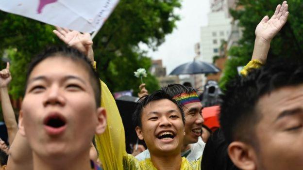 Activistas por los derechos de los homosexuales con paraguas y banderas de arco iris estallaron de alegría cuando se anunció el fallo.
