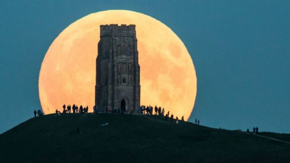 Luna gigante detrás de un edificio.