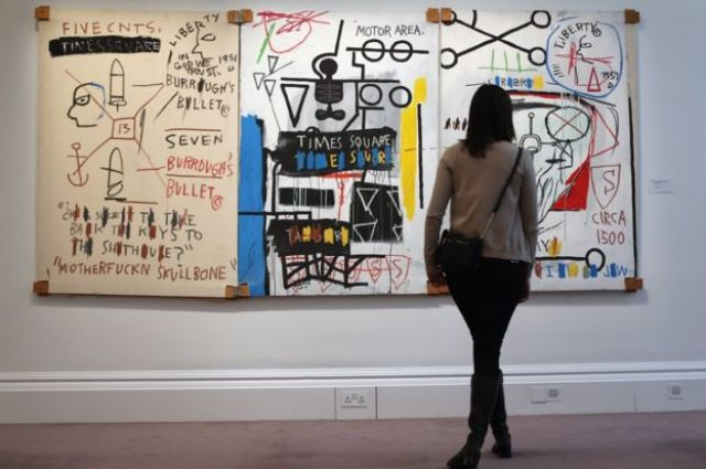 LONDON, ENGLAND - JANUARY 31: A visitor stands in front of a painting by Jean-Michel Basquiat entitled 'Five Fish Species,' on January 31, 2013 in London, England. The triptych painting is estimated to sell for between £4.25-6.25 Million GBP when it goes on sale at the 'Contemporary Art' evening sale at Sotheby's auction house on February 5, 2013. (Photo by Dan Kitwood/Getty Images)