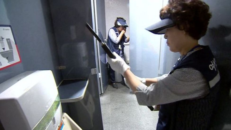 Inspector Park Gwang-Mi checking a public toilet for cameras