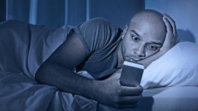 HOmbre viendo el celular en la cama.