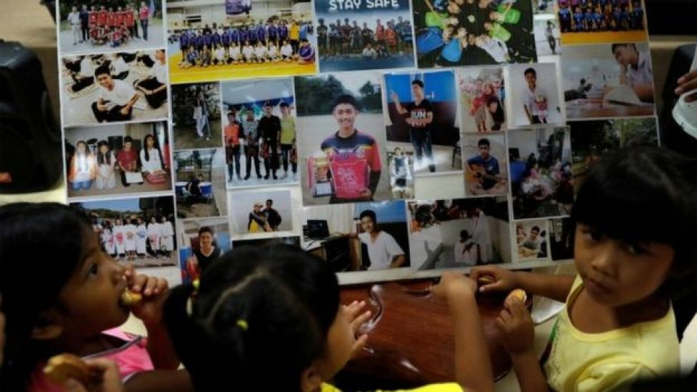 Children looks at photos of the trapped boys at a church in Chiang Rai