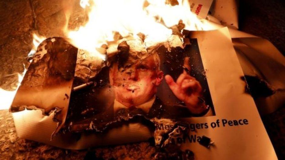 Manifestantes en Belén queman un póster de Mike Pence.
