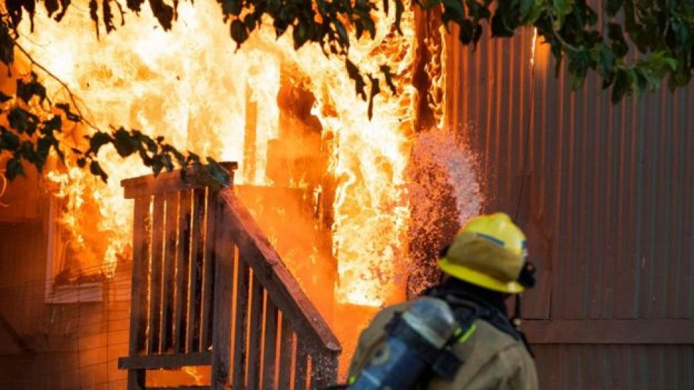 Firefighters battle an electrical fire in a mobile home park in Ridgecrest, California,