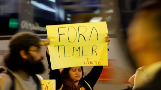 People hold a banner as they protest against Brazil's President Michel Temer in Sao Paulo, Brazil