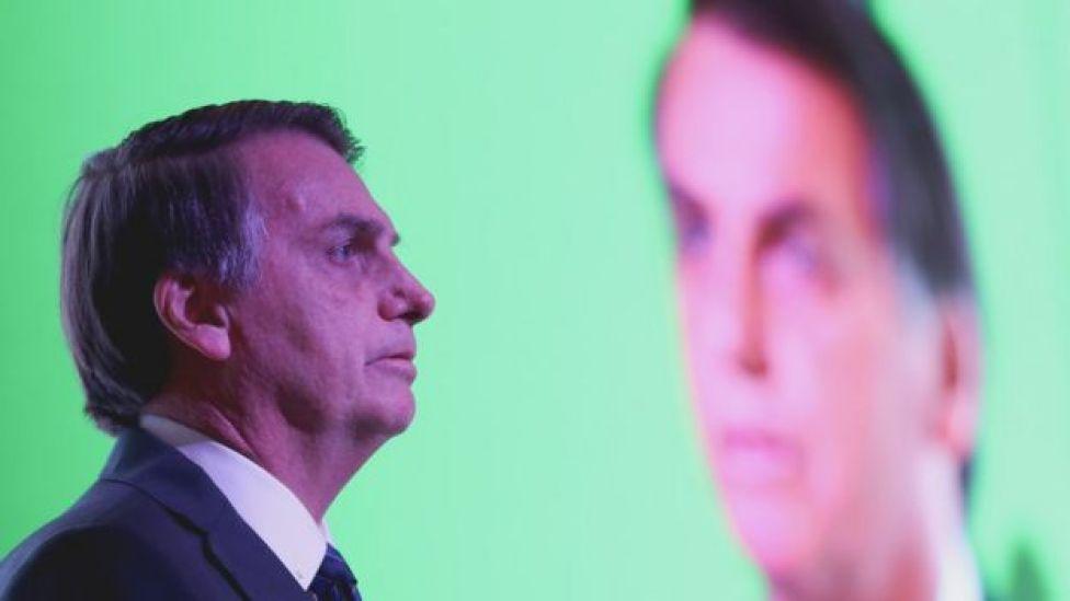 Bolsonaro aparece de perfil e, atrás, com sua imagem projetada no telão