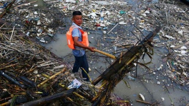 Homem em meio à lixo na China
