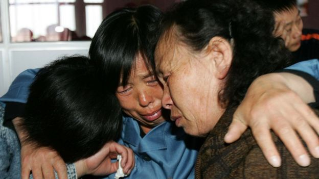 An inmate hugs her daughter and mother during a Mother's Day celebration at the Jilin Provincial Women's Prison 13 May 2007