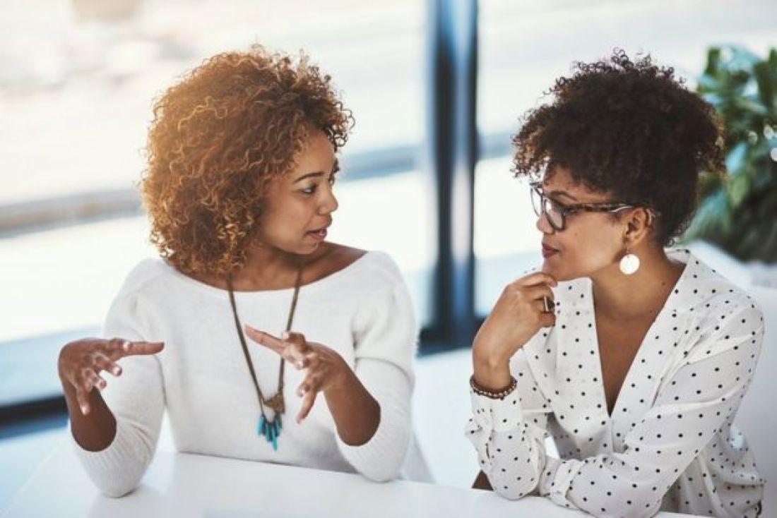 Dos mujeres jóvenes hablando y gesticulando.