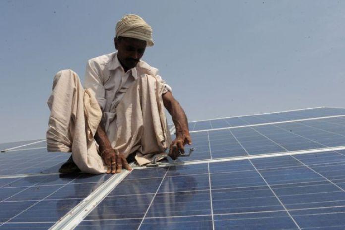 Obrero instalando páneles solares en India