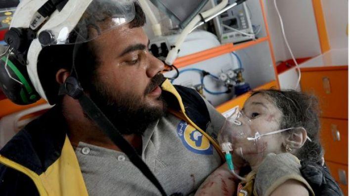 أحد عناصر الخوذ البيض يقدم المساعدة الطبية لطفلة سورية مصابة