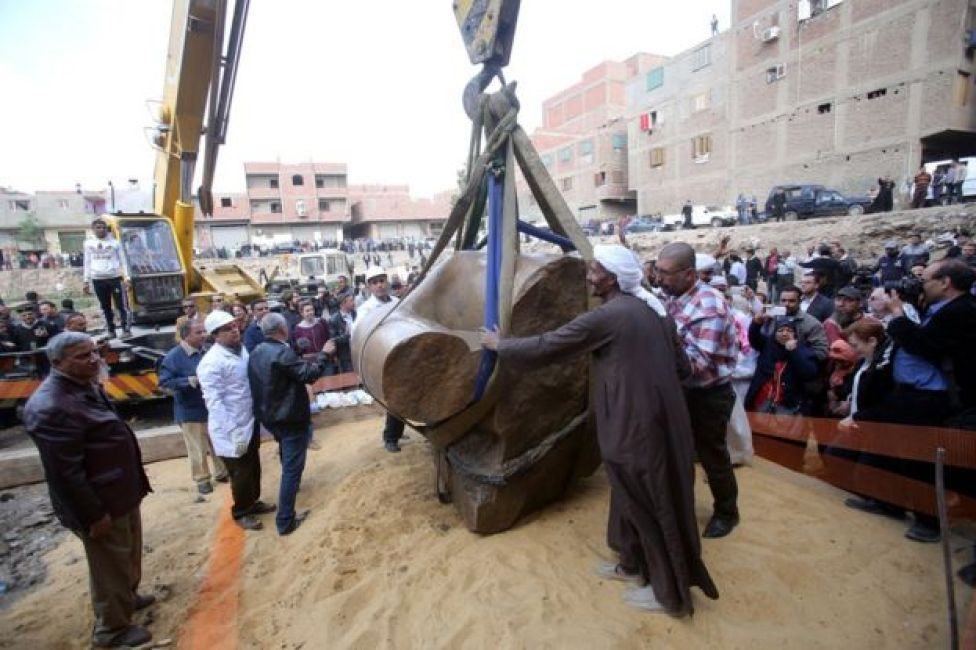 Egyptians look on as a crane lifts parts of a statue for restoration after it was unearthed at Souq al-Khamis district, at al-Matareya area, Cairo, Egypt, 13 March 2017