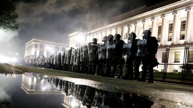 Riot police stand guard during a protest in Kenosha on 25 August
