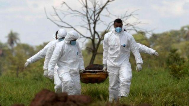 Homens carregam corpo resgatado em Brumadinho, MG