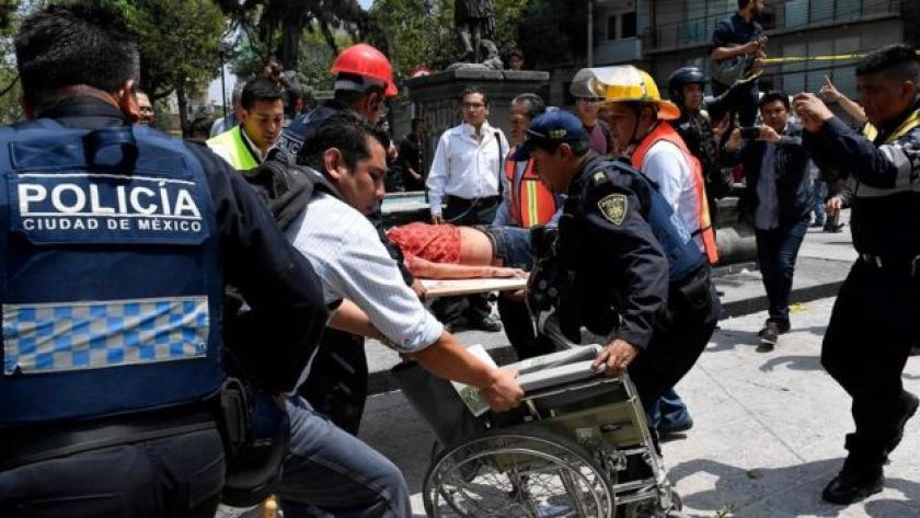 A woman is assisted after being injured during a quake in Mexico City