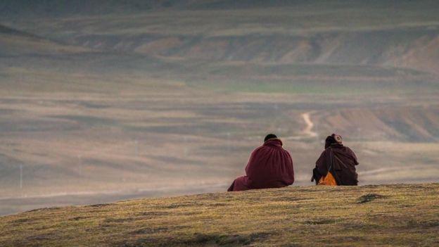 Dos tibetanos sentados en un paisaje montañoso, de espaldas