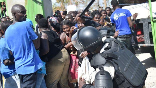 Personas tratando de entrar a un lugar donde se está entregando ayuda