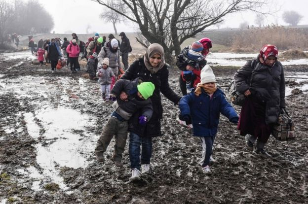 A woman helps her children walk through mud along with other migrants and refugees after crossing into Serbia via the Macedonian border.