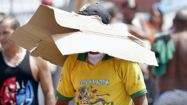 Hombre cubriéndose del sol con un cartón