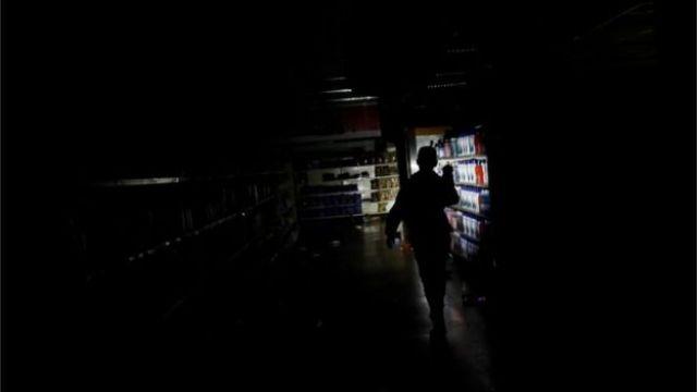 Funcionário de um mercado inspeciona os danos causados a uma loja saqueada em Caracas