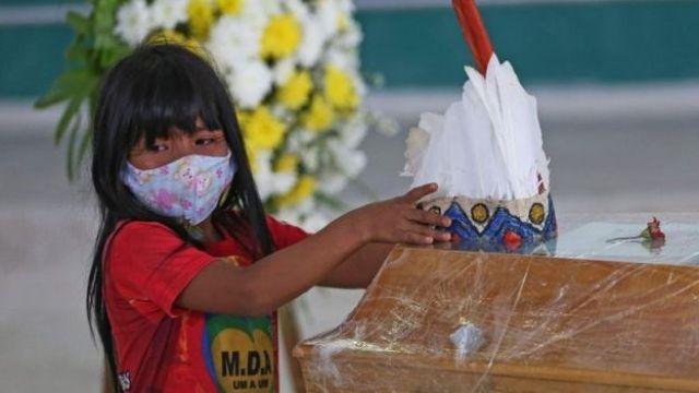 Criança indígena usando máscara coloca cocar sobre caixão no Brasil