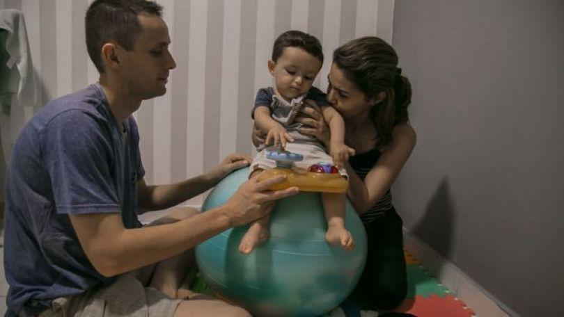 Imagem mostra o analista de sistemas Rinaldo Silveira, a nutricionista Michelle Costa e o filho Guilheme sentado sobre uma bola, tocando em um brinquedo. O menino tem 1 e 4 meses e foi diagnosticado em abril deste ano com Atrofia Muscular Espinhal (AME), uma doença rara e degenerativa que afeta entre 7 e 10 bebês a cada 100 mil nascidos vivos.